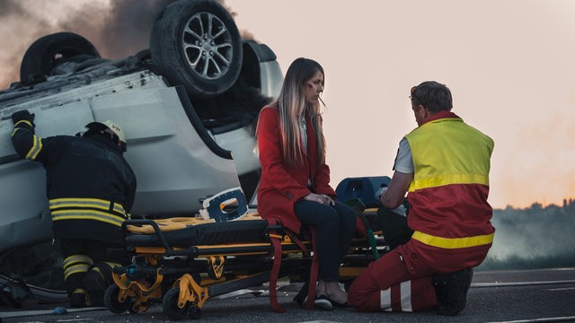 On the Car Crash Traffic Accident Scene: Paramedics Perform First Aid of a Female Victim who is Sitting on Stretchers. Rollover in the Background.
