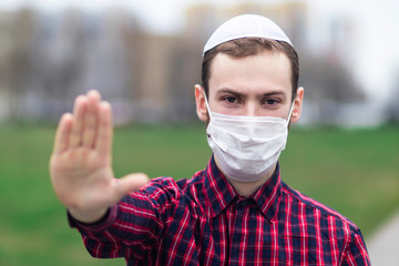 Wall Murals Palm tree Handsome young Jewish guy in traditional jewish male headdress, hat, boom, or yiddish on head. Man in medical mask on his face showing palm, stop sign against coronavirus, virus pandemic. Covid-19