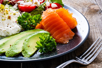 Breakfast - smoked salmon, cottage cheese, avocado and vegetable salad on wooden table