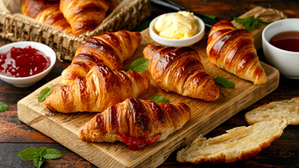Keuken foto achterwand Bakkerij Freshly baked croissants with butter, strawberry jam and tea for breakfast or brunch