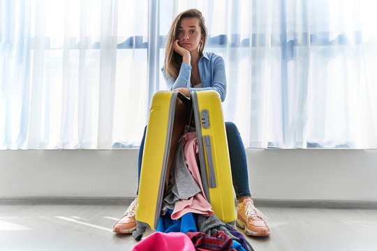 Portrait of upset woman traveler affected by flight delay and cancelled travel and vacation holidays. Travel ban and troubles while packing clothes in a yellow suitcase