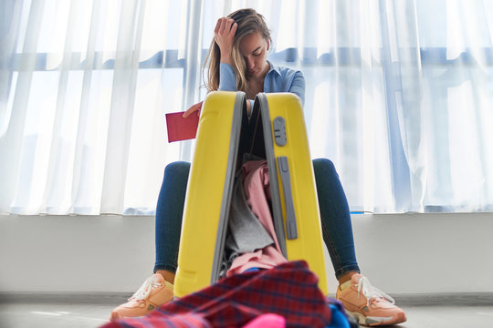 Upset woman traveler affected by flight delay and cancelled travel and vacation weekends holiday. Travel ban and traveling troubles. Problems while packing clothes in a suitcase