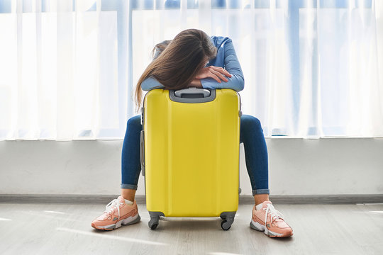 Woman traveler with yellow suitcase affected by flight delay and cancelled travel and vacation holiday. Travel ban and traveling troubles