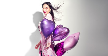 Spoed Fotobehang Beauty Valentine Beauty girl with colorful heart air balloons laughing, isolated on white background. Beautiful Happy Young woman. Holiday birthday party, having fun, celebrating with pink color balloon.