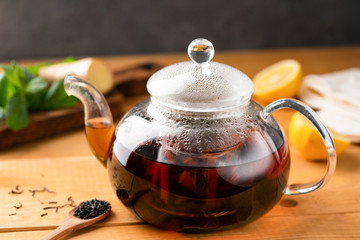 Foto op Textielframe Thee Glass tea pot with black tea on a wooden table. Healthy drink. Chinese tea with ginger, lemon and mint