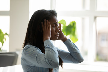 Unhappy african american businesswoman suffering from headache at work at laptop. Diverse female...