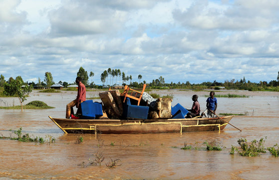 Residents use a boat to carry their belongings through the waters after their homes were flooded as the River Nzoia burst its banks and due to heavy rainfall and the backflow from Lake Victoria, in Budalangi within Busia County