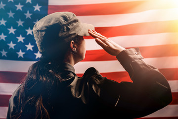 Veterans Day, Memorial Day, Independence Day.Silhouette of a female soldier saluting against the background of the American flag.Copy space.The concept of the American national holidays and patriotism Fotomurales