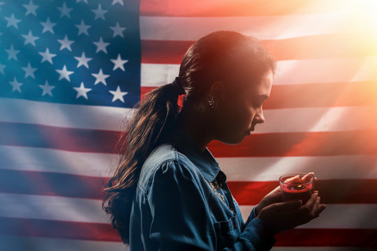 Memorial day. A woman holds a candle in memory of the victims. In the background, the American flag. Side view. Light. Concept of American holidays