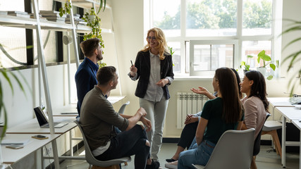 Smiling female leader, coach holding briefing for multiracial team interns in office, teaching students, plan to subordinates. Businesswoman at company meeting with diverse colleagues.