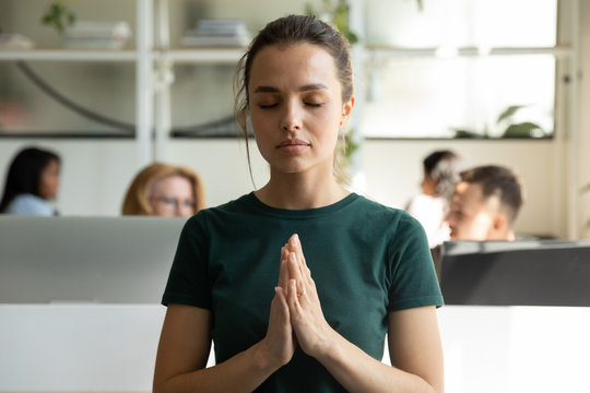 Close up confident attractive businesswoman closing eye relaxing using breath exercises. Stressful woman manager meditating for mind health. Calm and zen female mentor focusing and concentration.