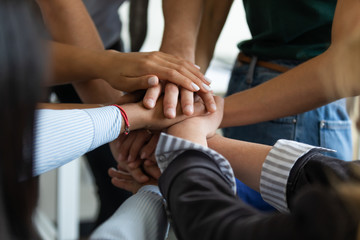 Close up multiracial business people putting hands together, showing support and unity. Diverse colleagues joining in team building activity, staff training concept, start working together, teamwork.