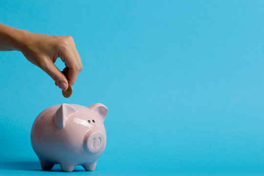 woman hand putting money coin into piggy for saving money wealth and financial concept