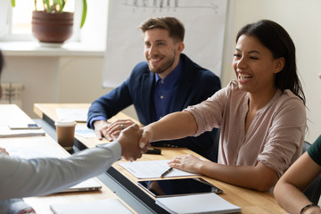 Happy laugh hr african american businesswoman shaking hand of applicant at interview. Diverse...