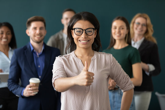 Portrait of african american businesswoman like gesture, showing thumbs up at camera. Different age diverse businesspeople standing behind of female company chief. Leader of multi-ethnic team concept