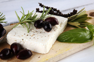 Greek cheese feta with rosemary and olives. Healthy ingredient for cooking salad. Chopped Goat feta cheese with gourmet herbs