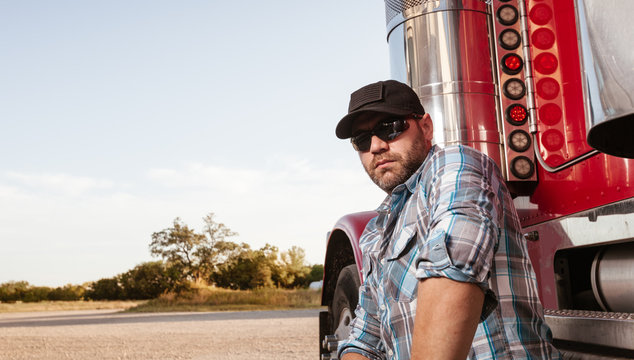 Casual dressed trucker with plaid shirt and baseball cap sits next to red big rig. Commercial driver looks confident at the camera. Self employed professional in transportation industry.
