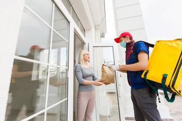Delivery Man standing with yellow thermo backpack for food delivery near the entrance home with empty space to copy paste