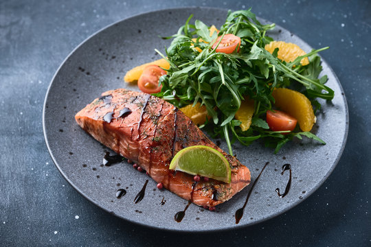 Hot smoked salmon with arugula salad, cherry tomato and orange. Healthy eating.