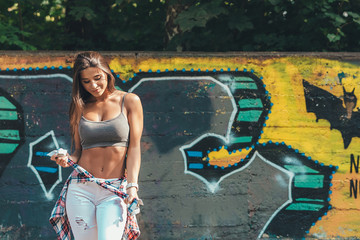 Relaxed young confident stylish woman tying shirt around waist on graffiti wall background