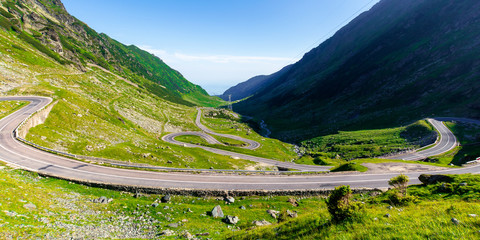 winding mountain road on a sunny day. empty highway run through valley. open vista in the distance. great european journey in summertime concept.