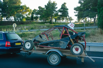 Car carrying trailer with an UTV off-road vehicle on highway road