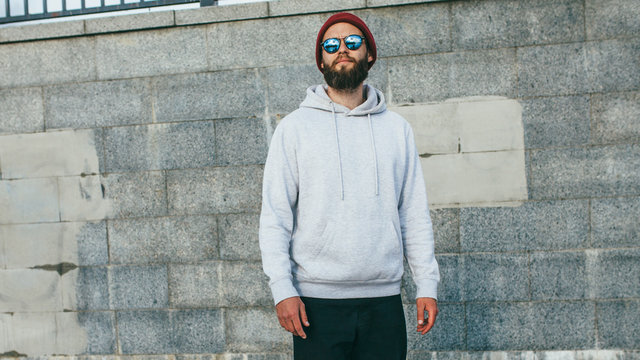 City portrait of handsome hipster guy with beard wearing gray blank hoodie or hoody with space for your logo or design. Mockup for print
