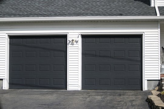 Two cars  Garage Door painted in black color in a typical single house.