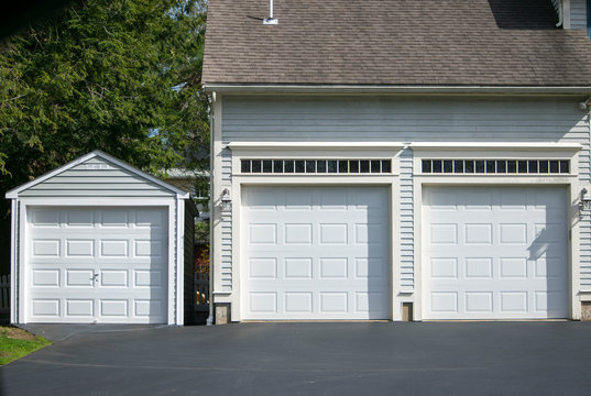 Two cars  Garage Doors painted in white color and one car garage attached to a in a multifamily  house.