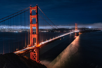 The iconic Golden Gate Bridge in San Francisico, California. Taken in the summer at night with long exposure, cars, city lights.