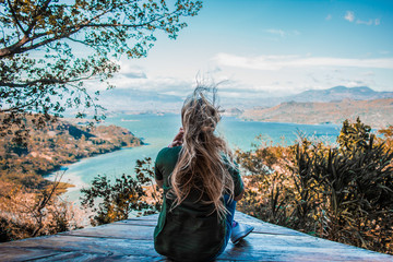Young woman watching the beautiful landscape of the lake between mountains