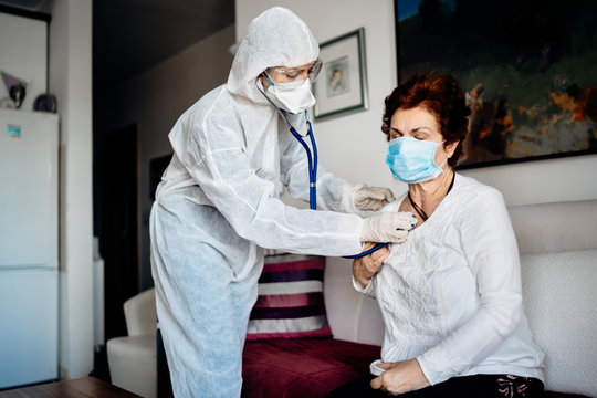 Home care doctor/nurse listening to the senior patients' lungs with a stethoscope.COVID-19 patient self isolation examination.Coronavirus frontline medical worker in home visit to high risk patient
