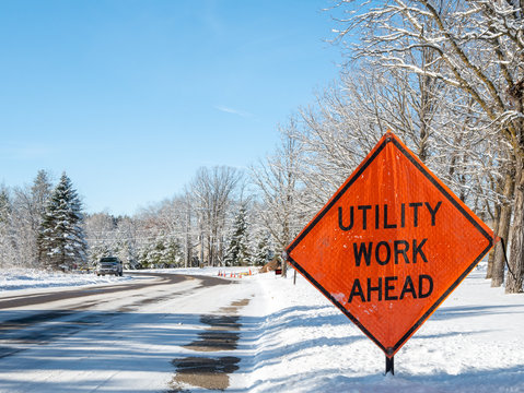 Orange UTILITY WORK AHEAD sign warns traffic about a work zone on a snowy city street, on a frosty and sunny winter day in Bemidji, Minnesota.