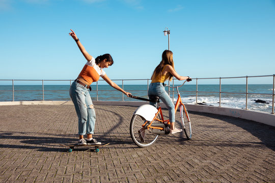 Side view of friends having fun with a skate and a bike
