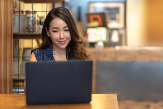 Smiling Pretty Asian woman making online reservation with laptop computer at Beautiful interior cafe. Young Charming Businesswoman relaxing and enjoying during doing video call meeting via internet,