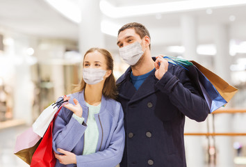 Papiers peints Ecole de Danse sale, consumerism and pandemic concept - happy young couple wearing face protective medical mask for protection from virus disease with shopping bags in mall