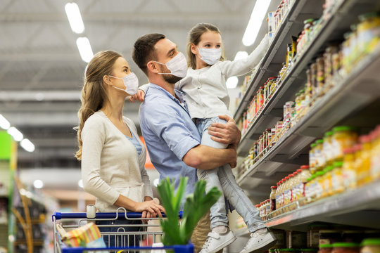 sale, family and pandemic concept - happy mother, father and daughter wearing face protective medical masks for protection from virus disease with shopping cart buying food at supermarket