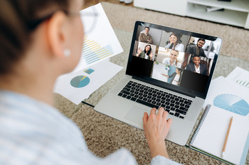 Business team working from home in a video conference. The back view of a girl who communicates online by video conference with her work colleagues using a laptop. Zoom conference Wall mural