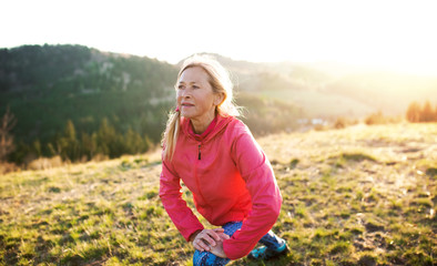 Attractive senior woman doing exercise outdoors in nature at sunset.