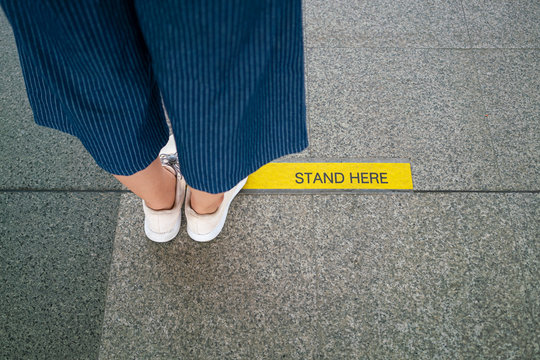 Asian woman standing on social distancing sign for keep distance and queue for entrance subway train a new normal life trend. corona virus, covid-19, social distancing or new normal concepts