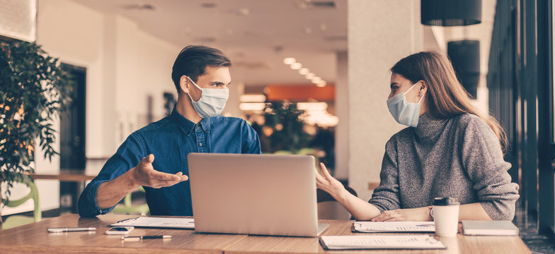 business colleagues in protective masks sitting at the office Desk.