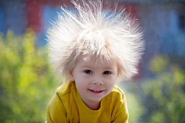 Cute little boy with static electric hair, having his funny portrait taken outdoors on trampoline