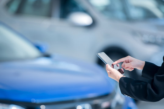 Women car salesmen use mobile smartphones at car showrooms. Check car sales in mobile phones to sell new cars.