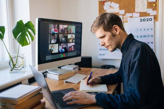 Man sitting by desktop computer and making notes. Working remotely Young man having video call via computer in the home office. Stay at home and work from home concept. Managing business team meeting