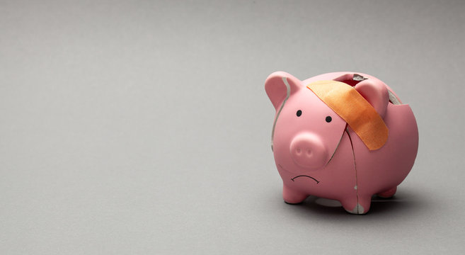 Broken piggy bank with band-aid on gray background