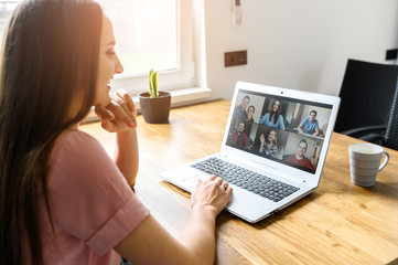 Communication on distance via video, video call, zoom. A young attractive woman using app on laptop for meeting with friends. She looks at webcam and smiles. Side view