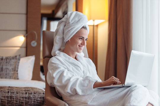 Positive successful young woman freelancer resting in a hotel room after a shower with bathrobe and towel working with a laptop while sitting at a table. Freelance success concept