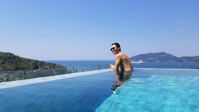 Asian man on vacation relaxing by luxery infinity pool on holidays with clear blue skies and crystal blue  aqua waters