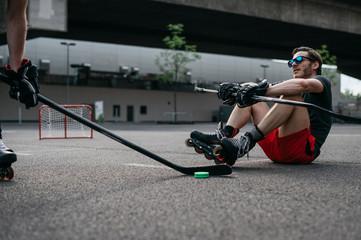 Men playing roller skate hockey outdoor on asphalt