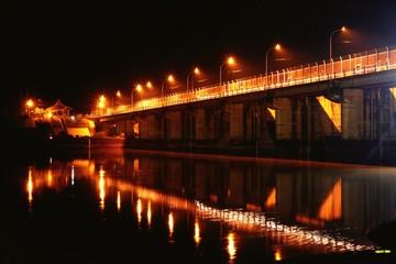 Fotomurales - Illuminated Bridge Over River In City At Night